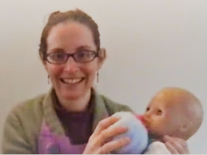 Screengrab of Emily with doll and knitted breast